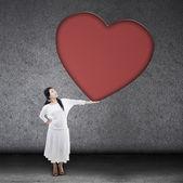 Beautiful woman holding blank heart sign — Stock Photo