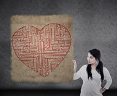 Beautiful woman holds heart maze map — Stock Photo