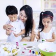 Teacher and children paints in classroom — Stock Photo #19727171