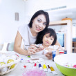 Mother and daughter paint easter eggs in house — Stock Photo #19727233