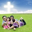 Happy Christian family on the grass — Stok fotoğraf
