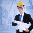 Architect holds blueprint plans — Stock Photo #20405647