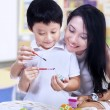 Beautiful mother teach son how to paint easter egg — Stock Photo #21135673