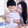 Beautiful mother teach son how to paint easter egg — Stock Photo