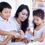 Happy teacher and preschooler paint easter eggs — Stock Photo