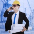 Manager holding blueprint and handphone - Stock Photo