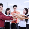 Business team joining hands in office — Stock Photo #21594195