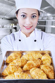 Baker brings croissant in kitchen — Stock Photo