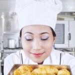 Asian baker smells bread — Stock Photo #22524751
