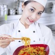 Asian chef and fried noodle in kitchen — ストック写真