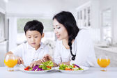Encourage child to eat salad at home — Stock Photo