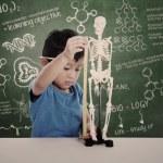 Asian kid measuring human skeleton model — Stock Photo #23338018