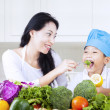 Mother feed brocolli to her child — Stock Photo #23338640