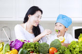 Mother feed brocolli to her child — Stock Photo
