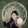Angry businesswoman ready to hit an alarm clock - Stockfoto