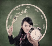 Angry businesswoman ready to hit an alarm clock — Stockfoto