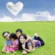Stock Photo: Happy family laying on the grass