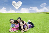 Happy family laying on the grass — Stock Photo