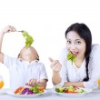 Eating vegetables with mother on white — Stock Photo