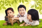 Three siblings and dog in park — Fotografia Stock