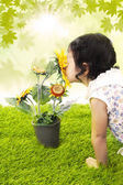 Girl kiss sunflower in spring — Stock Photo
