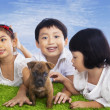 Children play with dog puppy — Stock Photo #23940751
