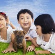 Children play with dog puppy — Stock Photo