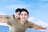 Asian couple pretend to fly over blue sky — Stock Photo