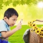 jongen vergroten bloemen in de tuin — Stockfoto #24126269