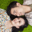 Happy couple lying on grass in the park — Stock Photo