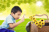 Boy magnify flowers in garden — Stockfoto