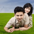 Happy couple lying on green grass — Stock Photo