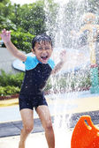 Happy boy play water in waterpark — Stock Photo