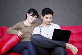 Happy couple looking at laptop on sofa — Stock Photo