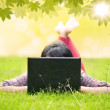 Asian student looking at laptop on green grass — Stock Photo