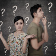Confused couple with question marks on blackboard — Stock Photo