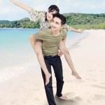 Asian couple having a good time on the beach — Stock Photo #24558789