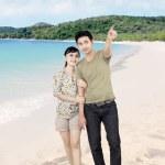 Asian boyfriend pointing at beach — Stock Photo #24613915