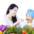Mother feed young chef — Stock Photo