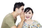 Boyfriend tell secret to girlfriend - isolated — Stock Photo