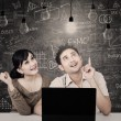 Couple looking at solution light bulbs in class — Stock Photo