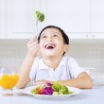 Happy boy eat brocoli in kitchen — Stock Photo #24693205