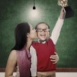 champion de l'école tenant le trophée baiser par maman en classe — Photo