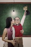 School champion holding trophy kiss by mum in class — Stock Photo