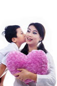Boy kiss mother holding heart shape pillow on white — Stock Photo