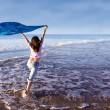 Girl running at beach with sarong — Stock Photo