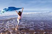 Girl running at beach with sarong — Stock Photo