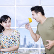 Husband angry at wife using megaphone - Stock Photo