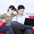Couple looking at laptop in apartment on red sofa — Stock Photo #25194917