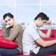 Couple stress sitting on red sofa - Stock Photo